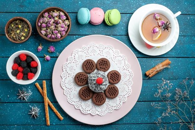 Biscoitos de chocolate saborosos com confitures e chá no bolo azul rústico de mesa, chá de cacau, biscoito doce, vista de cima