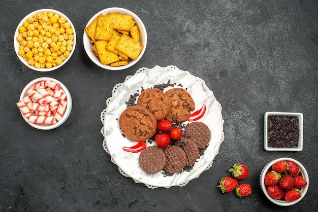 Biscoitos de chocolate saborosos com diferentes lanches em uma mesa escura de biscoitos de chocolate