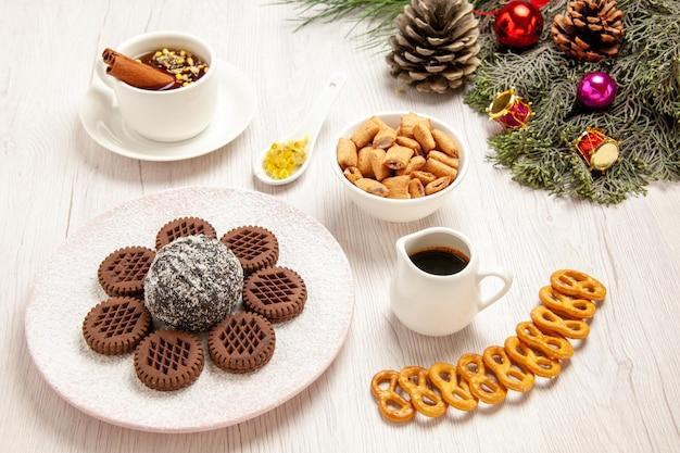 Biscoitos de chocolate saborosos de frente com bolinho de cacau e chá na mesa branca torta de chá biscoito doce