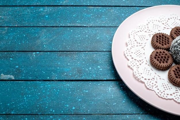 Biscoitos de chocolate saborosos de frente com bolo de chocolate na mesa rústica azul bolo de cacau chá de biscoito doce