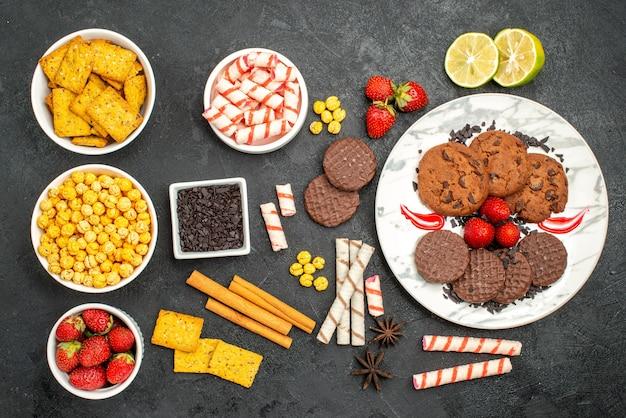 Biscoitos de chocolate saborosos de vista de cima com petiscos diferentes em fundo escuro.
