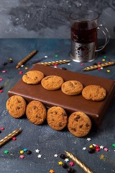 Biscoitos de chocolate saborosos de vista frontal na caixa marrom com pequenas estrelas coloridas, chá e velas na mesa cinza escuro, biscoito biscoito chá doce