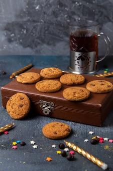 Biscoitos de chocolate saborosos de vista frontal na caixa marrom com pequenas estrelas coloridas e velas no fundo cinza escuro.