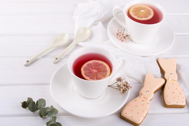 Biscoitos de coelhinho da páscoa e xícara de chá. configuração de mesa de café da manhã celebração. decorações de férias.