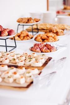 Biscoitos de confeitaria e croissants, sobremesas doces servidas em bebidas alimentares de evento de caridade e conceito de menu como banner de fundo de férias para design de marca de luxo