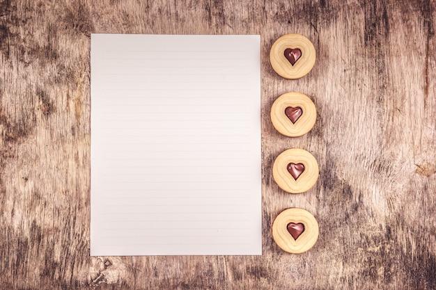 Biscoitos de coração com chocolate e folha de papel em branco sobre fundo de madeira