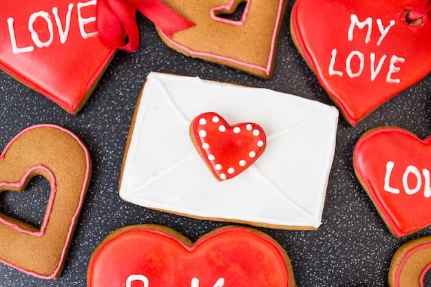 Biscoitos de coração com letra em fundo escuro