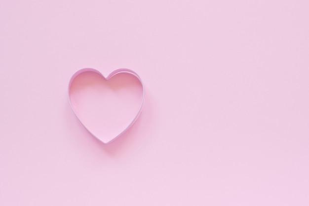 Biscoitos de cortador em forma de coração no fundo rosa pastel