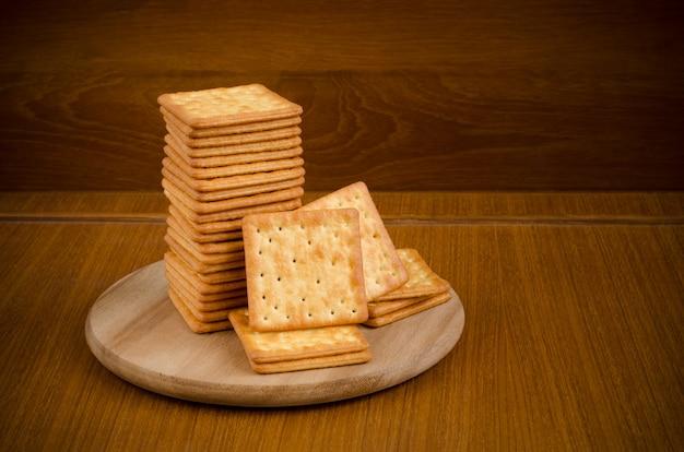 Biscoitos de creme fresco cozidos em pilhas sobre placa de círculo de corte de madeira