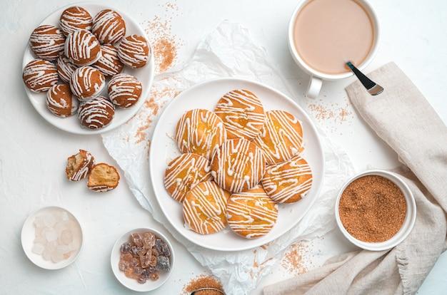 Biscoitos de diferentes tipos e uma xícara de café em um fundo branco.