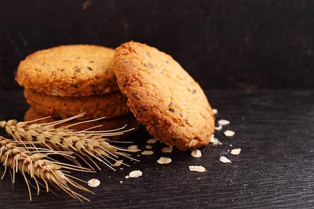 Biscoitos de farinha de aveia com grões em um fundo preto. foco seletivo.