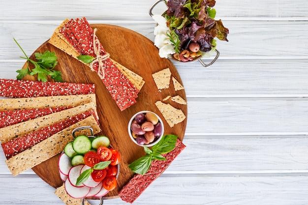 Biscoitos de farinha de beterraba e centeio com legumes para fazer lanches em uma parede de madeira. vegetarianismo e alimentação saudável