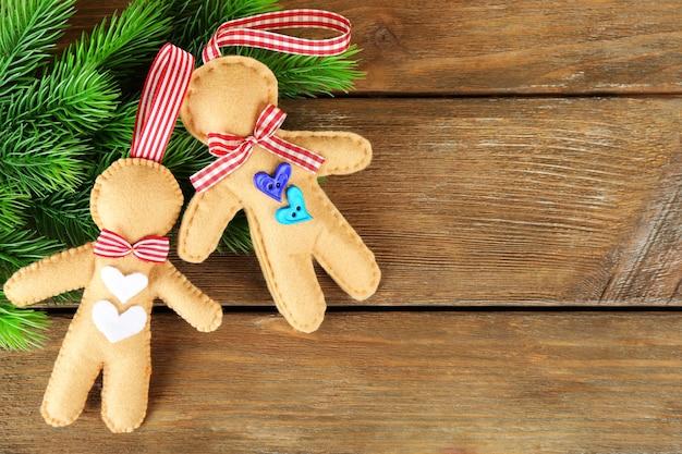 Biscoitos de feltro feitos à mão e botões de árvore do abeto no fundo de madeira