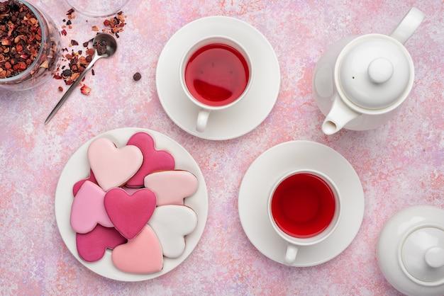 Biscoitos de forma de coração com glacê com chá de bagas. conceito: festa do chá de dia dos namorados, configuração de mesa festiva em rosa.