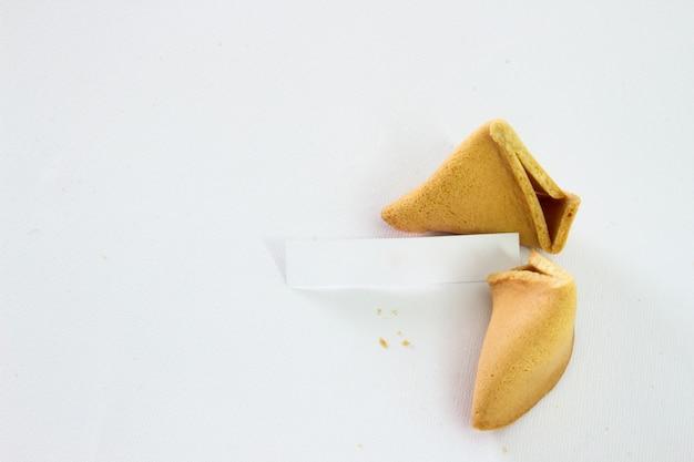 Biscoitos de fortuna quebrada com deslizamento em branco isolado no fundo branco
