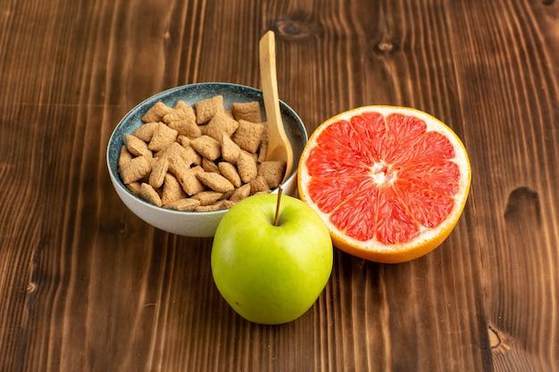 Biscoitos de frente com toranja e maçã na mesa de madeira marrom