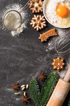 Biscoitos de fundo de pão de mel de natal com ingredientes para cozinhar, conceito de feriado de ano novo feliz na textura escura, cópia espaço vertical
