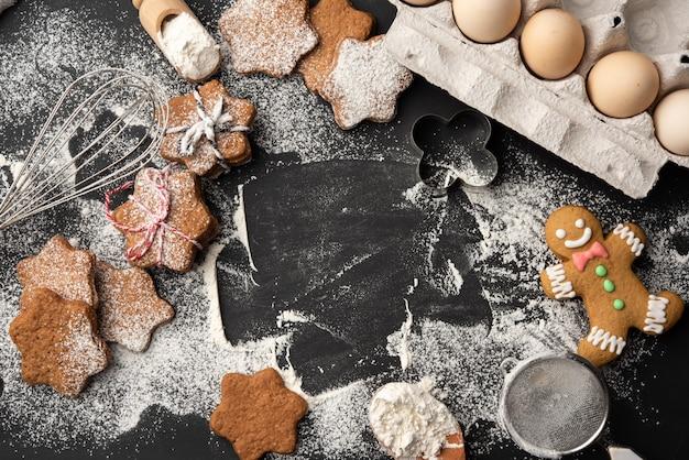 Biscoitos de gengibre assados em forma de estrela polvilhados com açúcar de confeiteiro em uma mesa preta, vista de cima