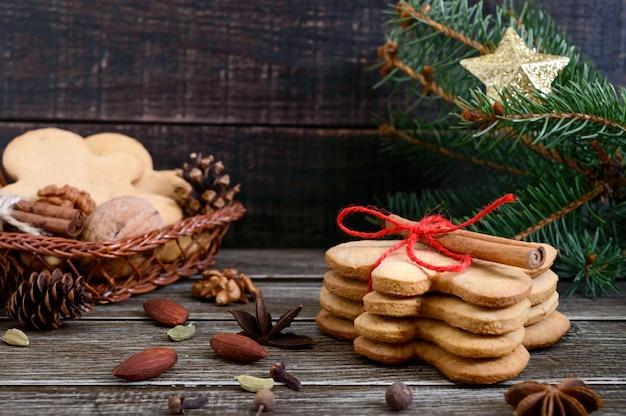 Biscoitos de gengibre caseiros de natal e especiarias no fundo de madeira