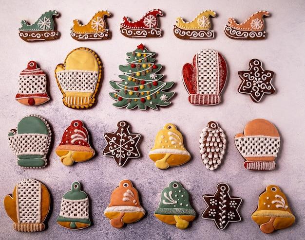 Biscoitos de gengibre caseiros de natal em plano de fundo cinza concreto, estilo knolling. floco de neve, abeto, estrela, trenó, cones, formato de sino em forma de cone