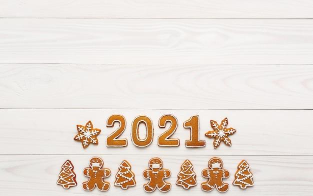 Biscoitos de gengibre caseiros de natal na forma de um homem mascarado e os números do ano novo na mesa de madeira branca. vista superior, copie o espaço
