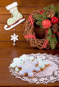 Biscoitos de gengibre caseiros, doces festivos de natal e ano novo em forma de cartão de fundo de flocos de neve azuis, em uma placa de madeira