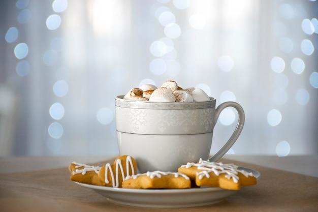 Biscoitos de gengibre caseiros e copo de bebida quente com luzes de marshmallow e bokeh branco no fundo.