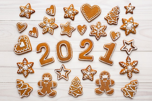 Biscoitos de gengibre caseiros em mosaico de natal na forma de um homem mascarado e os números do ano novo na mesa de madeira branca, vista superior
