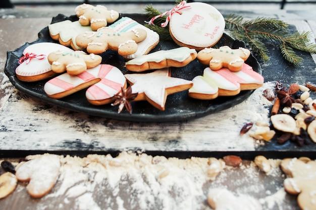 Biscoitos de gengibre coloridos na bandeja com farinha