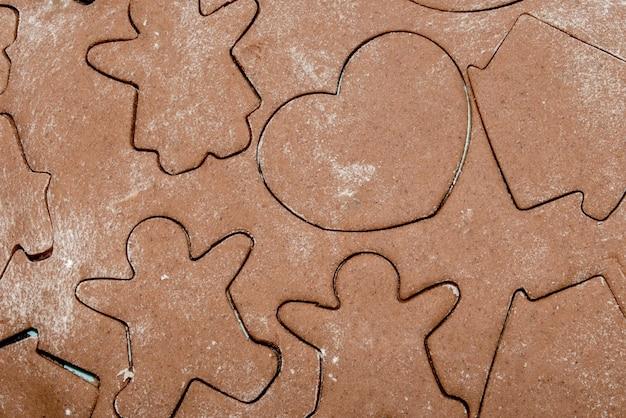 Biscoitos de gengibre, cortadores com massa em forma de flor.