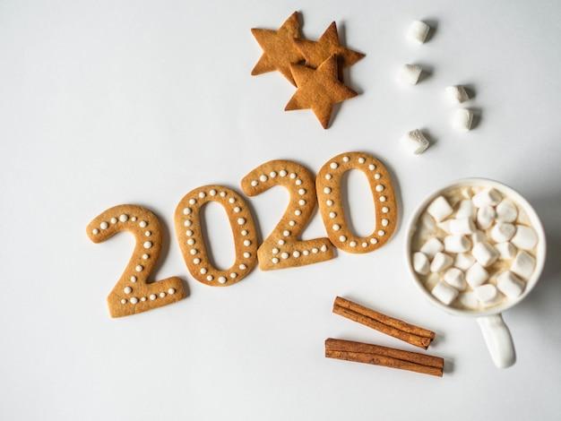 Biscoitos de gengibre de ano novo de 2020 e caneca de chocolate com marshmallows