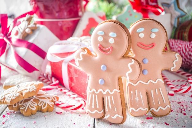 Biscoitos de gengibre de natal, com canecas festivas de chocolate quente, decoração e enfeites de natal, espaço de cópia de fundo branco