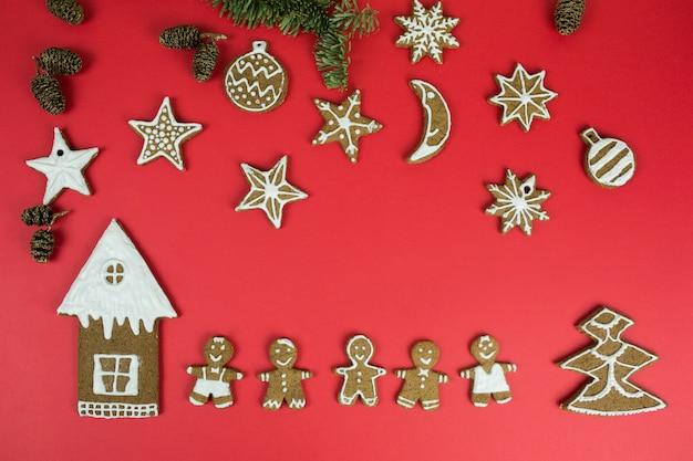 Biscoitos de gengibre de natal com decorações de ano novo em fundo vermelho. férias, natal, sobremesa, comida de ano novo, conceito de elementos de design