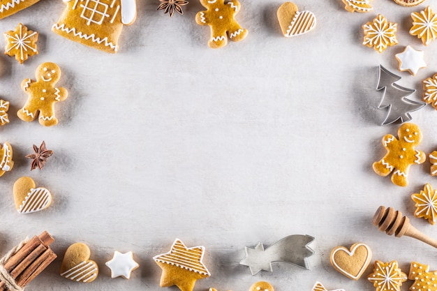 Biscoitos de gengibre de natal deita sobre a mesa junto com canela e pinhas - copie o espaço.