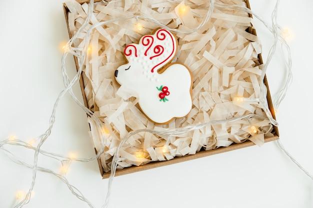 Biscoitos de gengibre de natal e ano novo e luz de natal. em forma de cervo. vista do topo. fundo branco. estilo minimalista.