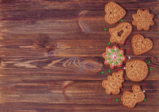 Biscoitos de gengibre de natal e aspersão para decoração em fundo de madeira rústico com espaço em branco para texto. vista superior, configuração plana.