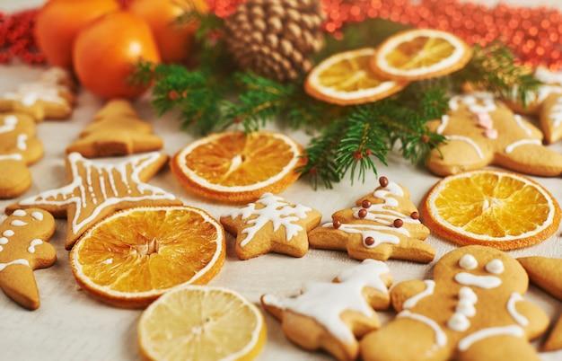 Biscoitos de gengibre de natal e laranja seca e especiarias na mesa branca. cadeiras árvores de natal, cones e decorações de natal