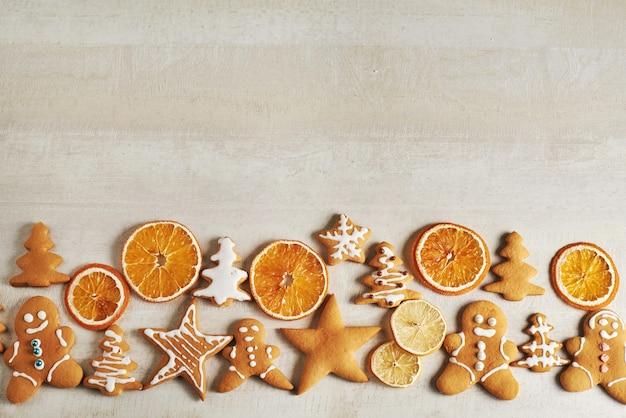 Biscoitos de gengibre de natal e laranja seca e especiarias na mesa branca