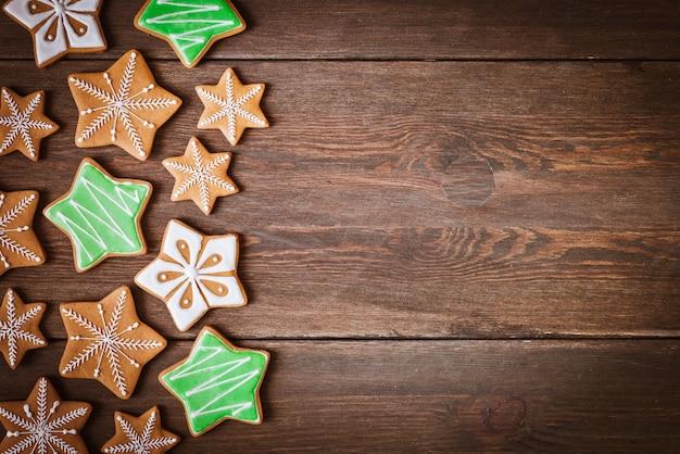 Biscoitos de gengibre de natal em forma de estrelas encontra-se em um fundo de madeira.