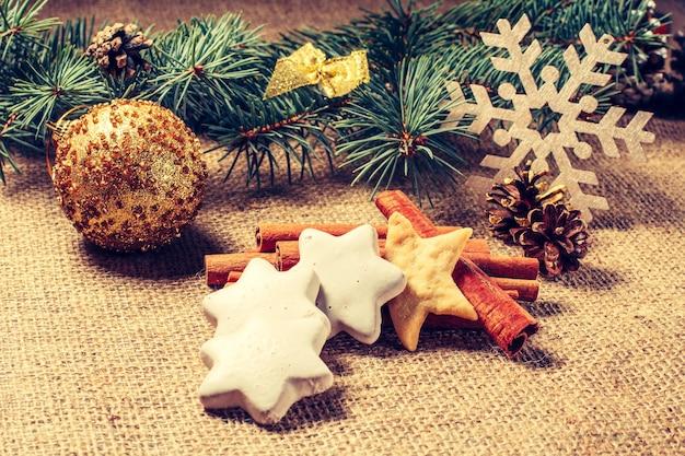 Biscoitos de gengibre de natal em saco com canela, anis estrelado, bola brilhante, floco de neve decorativo e galhos de árvores de abeto naturais com cones. efeito de tonificação de cor.