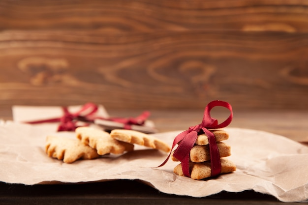 Biscoitos de gengibre de natal na placa de madeira escura.