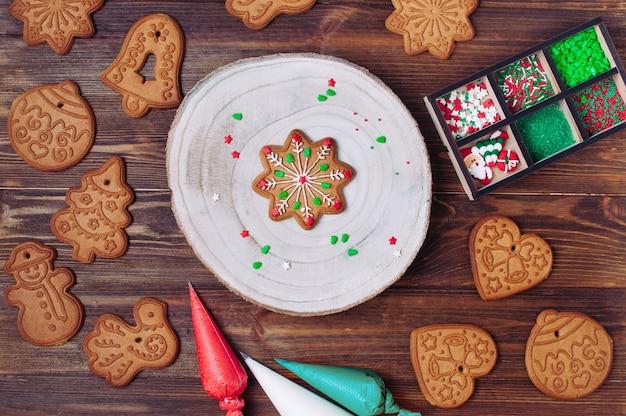 Biscoitos de gengibre de natal, sacos de confeiteiro de cor e aspersão para decoração em superfície de madeira rústica. vista superior, configuração plana.