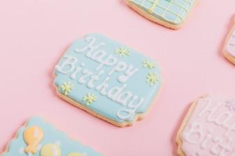 Biscoitos de gengibre de texto de aniversário no pano de fundo rosa