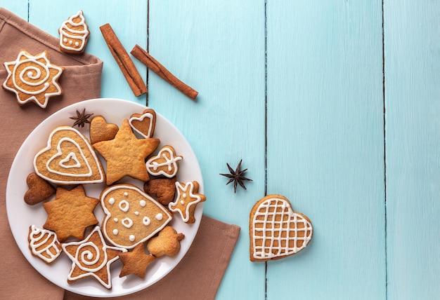 Biscoitos de gengibre decorados com glacê em um prato sobre um fundo azul de madeira