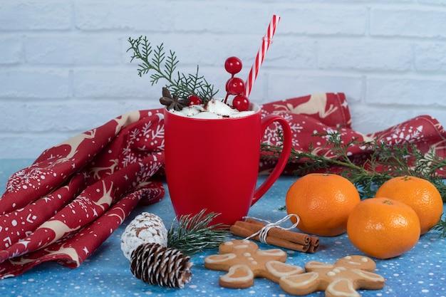 Biscoitos de gengibre deliciosos, tangeriens e xícara de café vermelha no azul.
