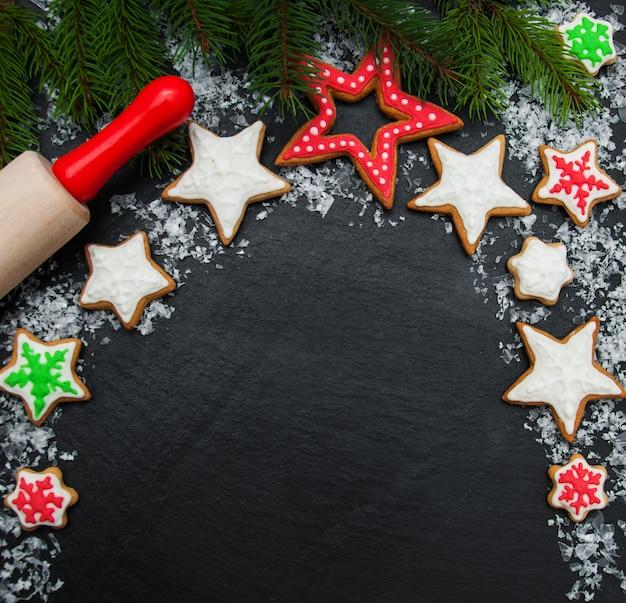 Biscoitos de gengibre e mel de natal no quadro de fundo escuro