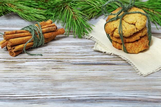 Biscoitos de gengibre e paus de canela com galhos de pinheiro.