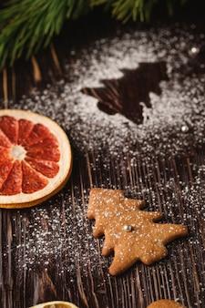 Biscoitos de gengibre em forma de abeto de natal, açúcar em pó na mesa de madeira, frutas cítricas secas, galho de árvore do abeto, vista de ângulo, foco seletivo
