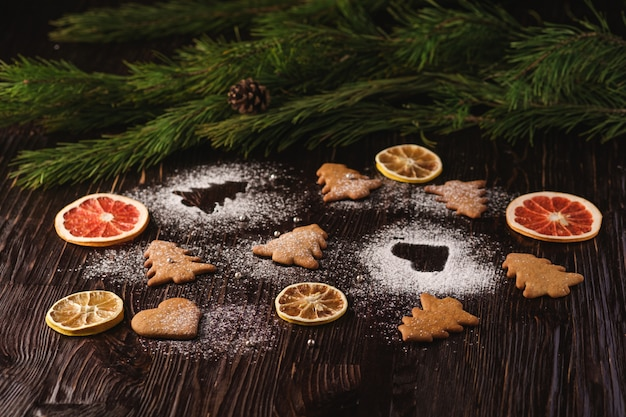 Biscoitos de gengibre em forma de abeto e coração de natal, açúcar em pó na mesa de madeira, frutas cítricas secas, galho de árvore do abeto, vista de ângulo, foco seletivo