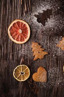 Biscoitos de gengibre em forma de abeto e coração de natal, açúcar em pó na mesa de madeira, frutas cítricas secas, vista superior